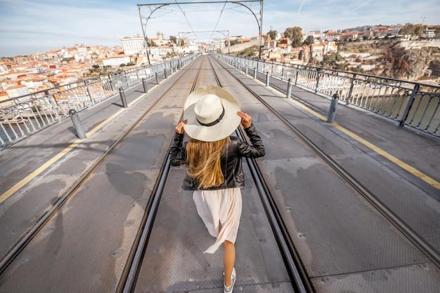 Blick auf die luis-brücke mit junger frau, die bei sonnigem wetter in der stadt porto, portugal, zurückgeht