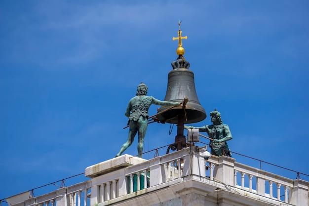 Blick auf die mauren, die die stunden an der spitze des markusturms in venedig, italien, schlagen
