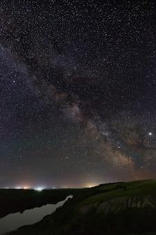 Blick auf die milchstraße über den fluss. helle sterne des nachthimmels