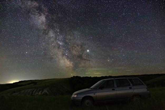 Blick auf die milchstraße über die autofahrer. helle sterne des nachthimmels. astrofotografie mit langzeitbelichtung.