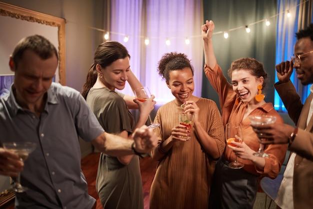 Blick auf die multiethnische gruppe von freunden, die die party drinnen genießen und fröhlich zusammen tanzen