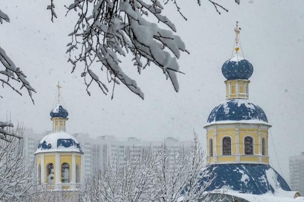 Blick auf die petropavlovskaya-kirche im herbst in yasenevo bei schneefall.
