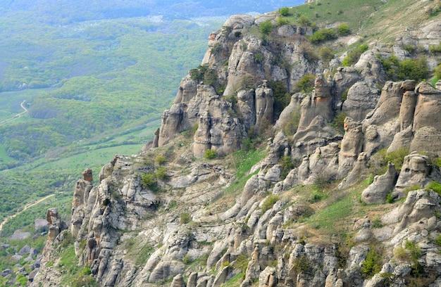 Blick auf die riesigen felsigen klippen und das grüne tal mit wald bedeckt. schöne berglandschaft