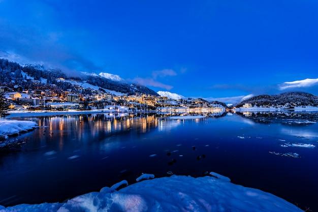 Blick auf die schönen nachtlichter der stadt st. moritz in der schweiz bei nacht im winter mit reflexion vom see und den schneebergen im hintergrund