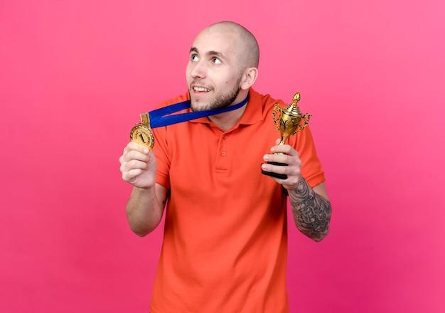 Blick auf die seite erfreut jungen sportlichen mann, der medaille mit siegerpokal trägt und hält