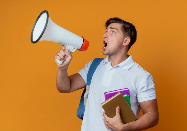 Blick auf die seite junger hübscher männlicher student, der rückentasche hält bücher hält und auf lautsprecher spricht