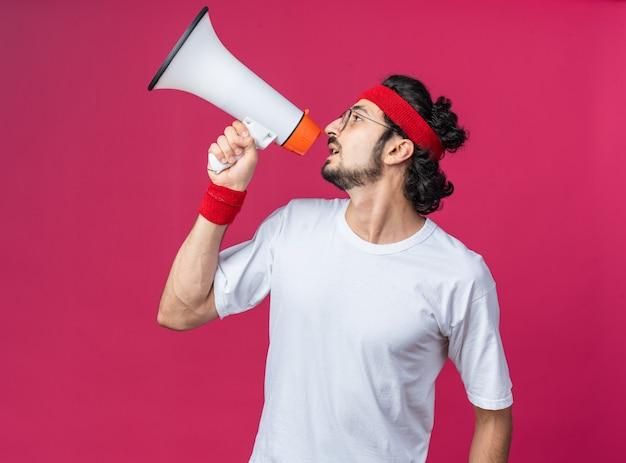 Blick auf die seite junger sportlicher mann mit stirnband mit armband spricht über lautsprecher