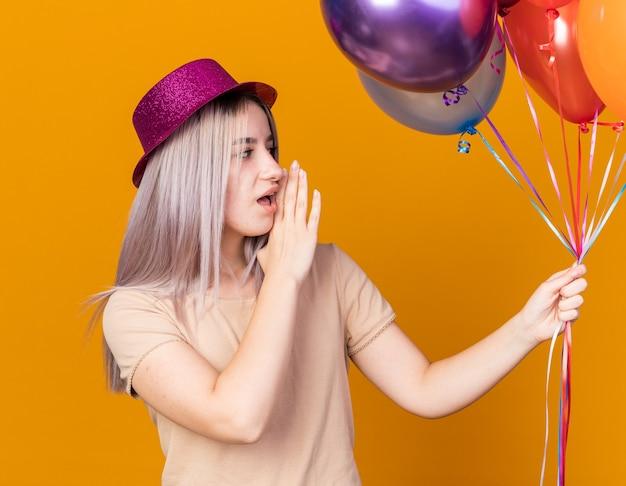 Blick auf die seite junges schönes mädchen mit partyhut mit luftballons flüstert isoliert auf oranger wand
