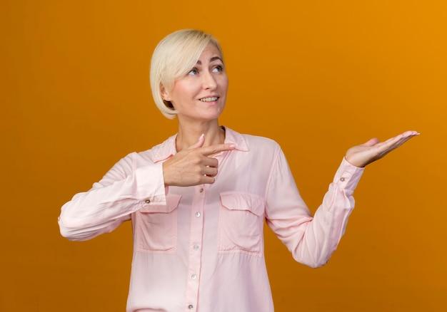 Blick auf die seite lächelnde junge blonde slawische frau, die vorgibt und auf etwas zeigt
