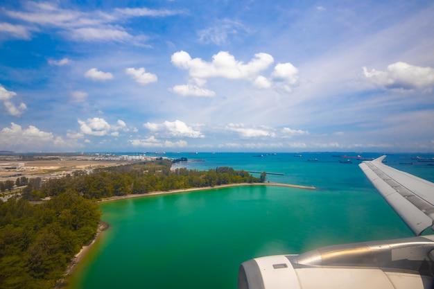 Blick auf die tropische ozeanküste aus dem bullauge eines landeflugzeugs. urlaubsreise