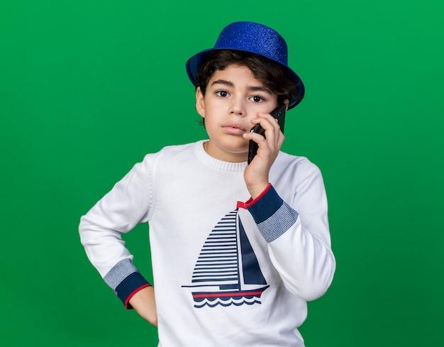 Blick auf die vorderseite kleiner junge mit blauem partyhut spricht am telefon und legt die hand auf die hüfte, isoliert auf grüner wand