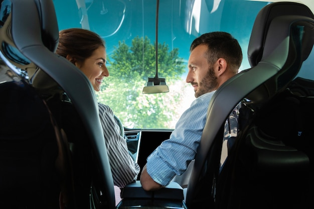 Blick auf ehemann. strahlende glückliche frau, die ihren mann anschaut, nachdem sie das auto geparkt hat