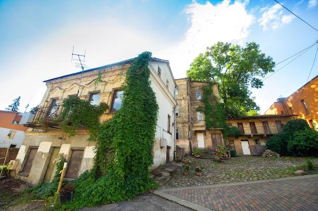 Blick auf ein altes wohnhaus mit gepflasterten pflastersteinen. grüne pflanzen an einem haus in vilnius, litauen.