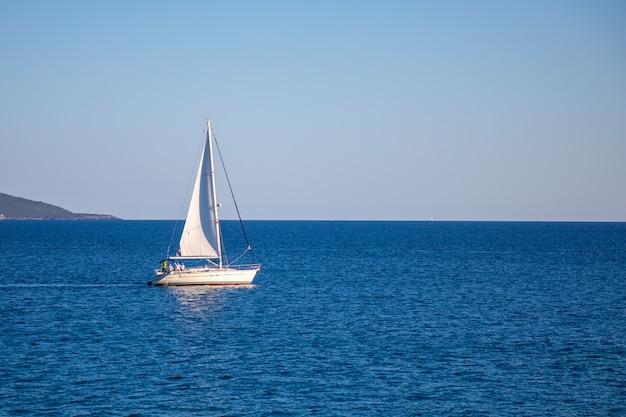 Blick auf ein kleines yachtboot, das in ruhiger offener see in montenegro segelt