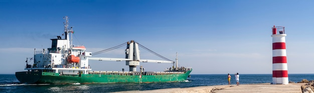 Blick auf ein langes fischereischiff, das durch die ria formosa-sümpfe auf faro, algarve, austritt.