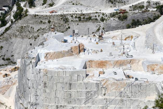 Blick auf ein marmorsteinbruch-tal in carrara, toskana, italien, das geschnittene steinblöcke und eine terrassierte felswand im tagebau zeigt