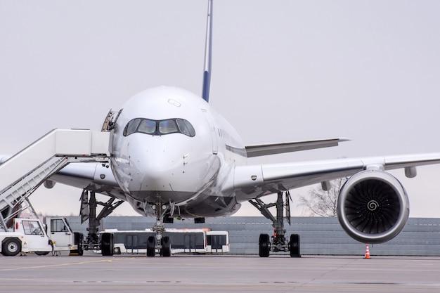 Blick auf ein passagierflugzeug mit großer reichweite am flughafen mit einer rampe auf dem parkplatz.