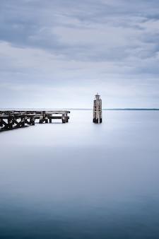 Blick auf ein ruhiges meer in der nähe eines holzdocks an einem düsteren tag