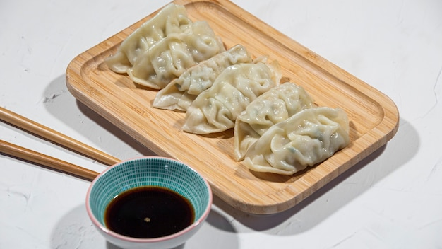 Blick auf ein tablett mit japanischen gyoza-vorspeisen in einem restaurant oder einer küche.