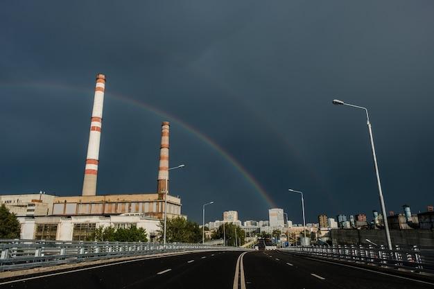 Blick auf ein wärmekraftwerk mit regenbogen.