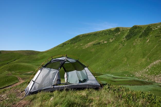Blick auf ein zelt zwischen bergen. kleiner campingplatz in der nähe des sees in den karpaten in der morgenzeit. sommersaison und konzept der erholung und entspannung, allein mit der natur.