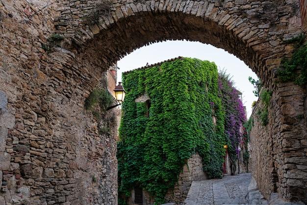 Blick auf eine blühende straße im mittelalterlichen dorf peratallada in girona, katalonien, spanien.
