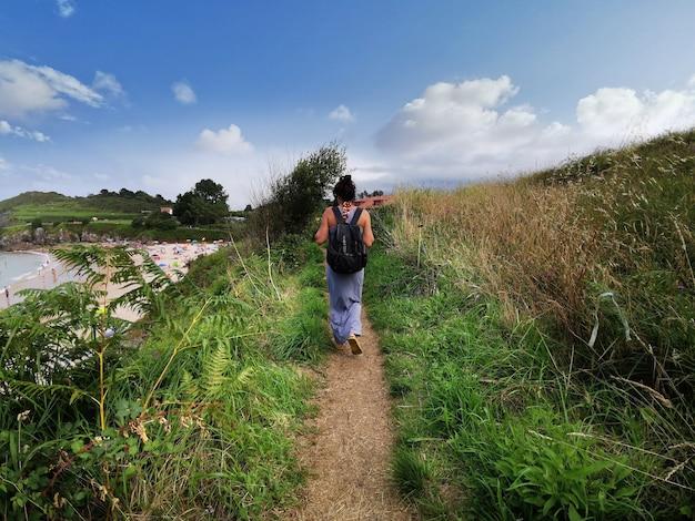 Blick auf eine frau von hinten, die einen weg entlang geht die natur genießen
