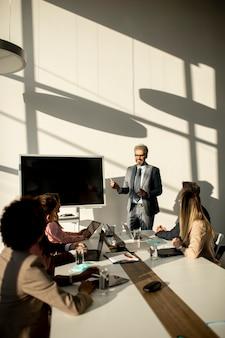 Blick auf eine gruppe von geschäftsleuten, die zusammenarbeiten und ein neues projekt auf einem meeting im büro vorbereiten