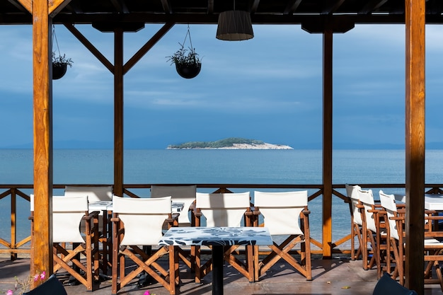 Blick auf eine insel und das ägäische meer vom leeren restaurant