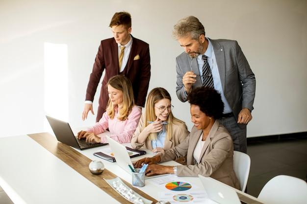 Blick auf eine multiethnische gruppe von geschäftsleuten, die zusammenarbeiten und ein neues projekt für ein treffen im büro vorbereiten