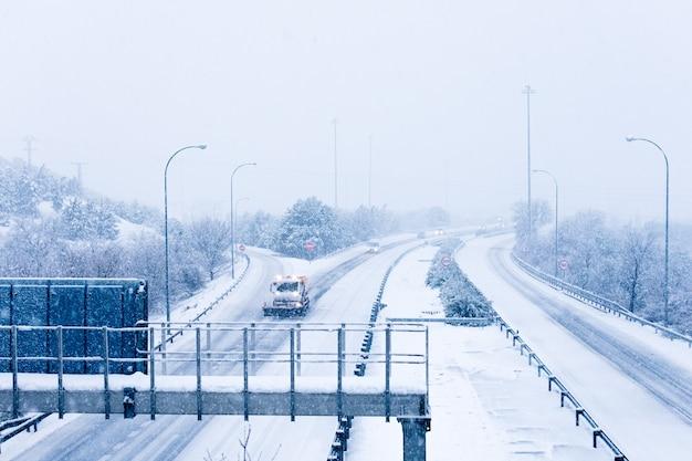 Blick auf eine schneebedeckte spanische autobahn und einen schneepflug, der schnee entfernt.
