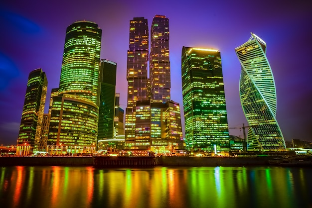 Blick auf eine stadt mit beleuchteten wolkenkratzern bei nacht