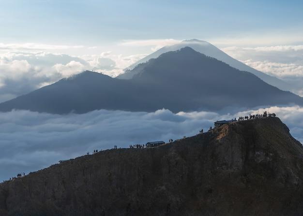 Blick auf einen berg und menschen, die über die felsen in indonesien gehen