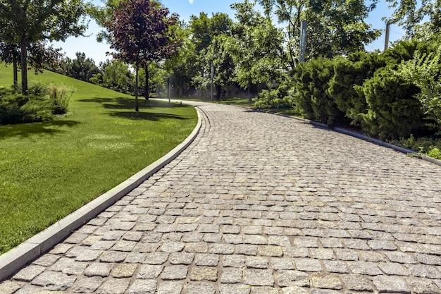 Blick auf einen breiten gepflasterten weg zum wandern, umgeben von grünen büschen und bäumen im gepflegten park an sonniger s...