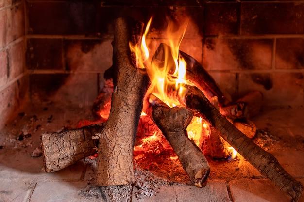Blick auf einen brennenden kamin. textur eines brennenden baumes. helles feuer