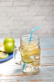Blick auf einen krug limonade mit eis neben einigen zitronenscheiben und limetten