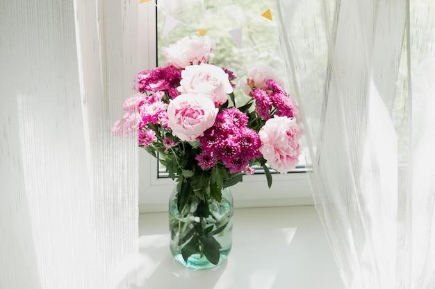 Blick auf einen strauß rosa pfingstrosen und chrysanthemen in einer vase am fenster. konzept hintergrund, blumen, urlaub.