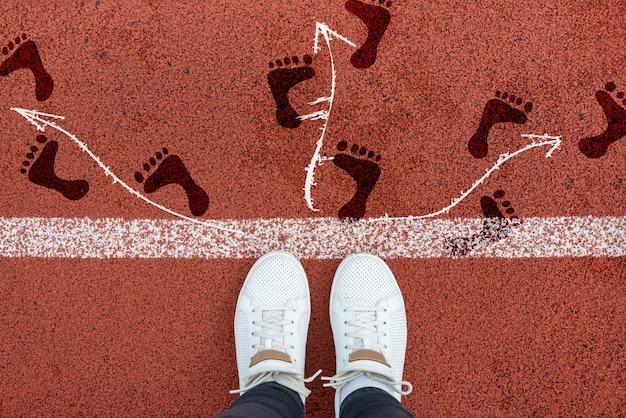 Blick auf graue füße und pfeile, die auf einem roten laufband in verschiedene richtungen zeigen. entscheidungsfindung und wahl. finden sie ihren eigenen weg. bewegungsrichtung, kreuzung