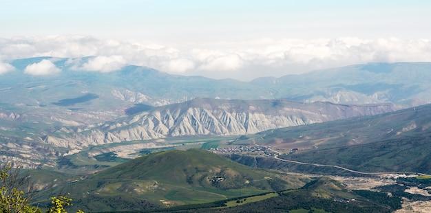 Blick auf grüne berge und dörfer im tal. weitwinkelpanorama