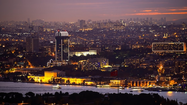 Blick auf istanbul bei nacht, mehrfachbeleuchtung, niedrige und hohe gebäude, bosporus-straße im vordergrund, türkei