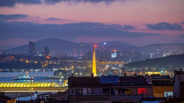 Blick auf istanbul bei nacht, mehrfachbeleuchtung, niedrige und hohe gebäude, bosporus-straße mit schwimmenden schiffen, türkei
