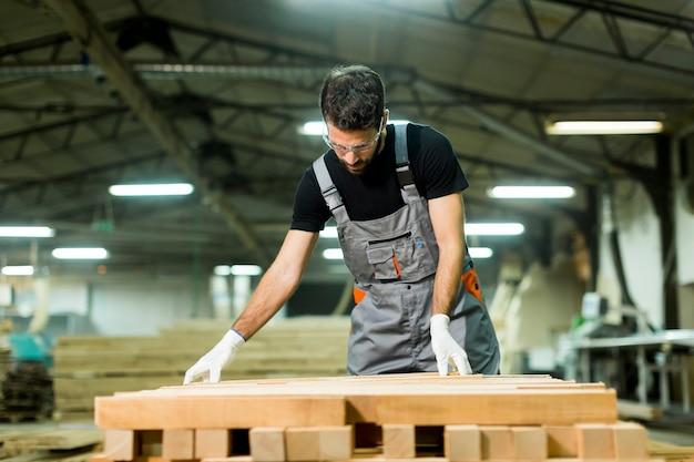 Blick auf junge arbeiter arbeitet in einer fabrik für die herstellung von möbeln
