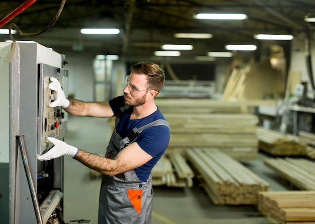 Blick auf jungen mann arbeitet in einer fabrik für die herstellung von möbeln