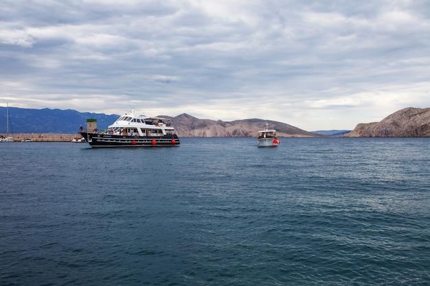 Blick auf meer, berge und schiff bei bewölktem wetter.