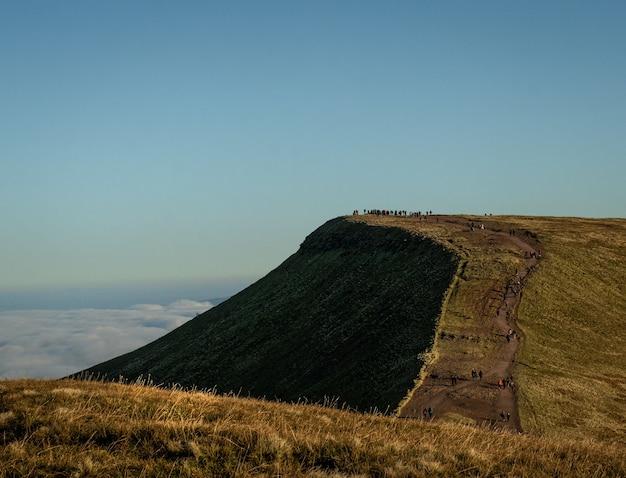 Blick auf menschen, die auf die klippe eines berges zugehen