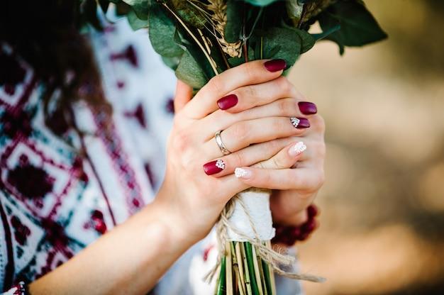 Blick auf ring, maniküre und handbräute halten blumenstrauß auf rustikalen herbst.