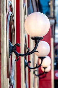 Blick auf rotes gebäude mit weißen glaskugellampen in reihe