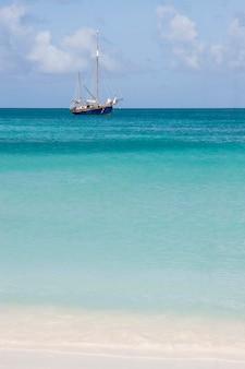 Blick auf schönen tropischen strand mit einem segelboot