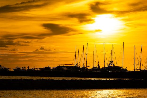 Blick auf sonnenuntergang und silhouetten von yachten auf dem see