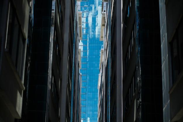 Blick auf vollglasgebäude zwischen zwei bürogebäuden